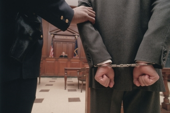 Man in Handcuffs Stands in a Courtroom